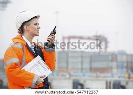 Side view of female engineer using walkie-talkie in shipping yard