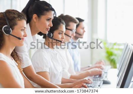 Side view of female manager assisting her staffs in a call center - stock photo