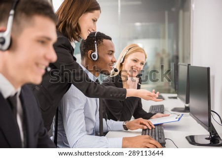Side view of female manager assisting her staffs in a call center. - stock photo