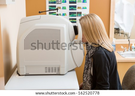 Side view of female patient going through eye examination in clinic - stock photo