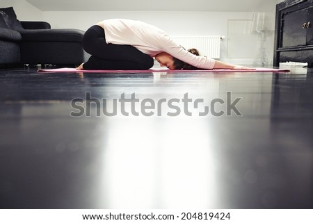 Side view of fit young lady practicing yoga at home. Healthy woman exercising in living room. - stock photo