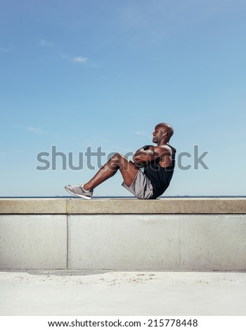 Side view of fit young man exercising outdoors. Muscular young man doing sit-ups against sky. - stock photo