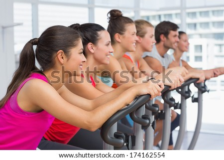 Side view of fit young people working out at class in gym - stock photo