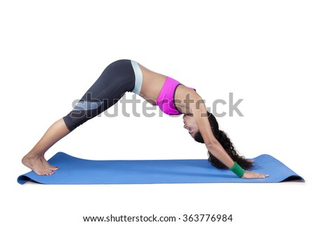 Side view of fit young woman doing the Downward Facing Dog pose on exercise mat