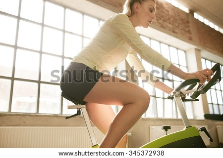 Side view of fitness woman on bicycle in gym. Young female athlete on bicycles at health club. - stock photo