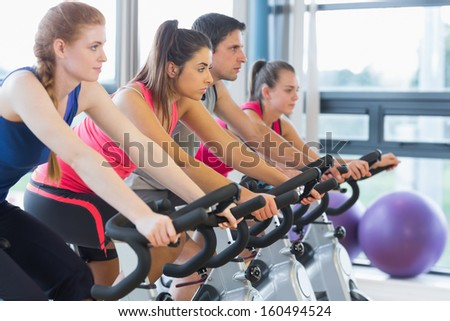 Side view of four people working out on exercise bikes - stock photo