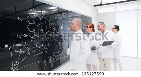 side-view of four scientists in a chemistry lab analyzing formulas on a blackboard - stock photo
