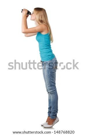 Side view of full length blond woman looking through binoculars sideways - stock photo