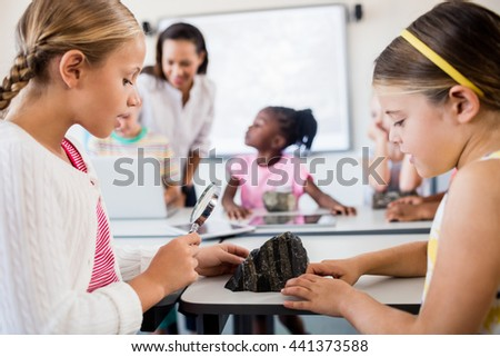 Side view of girls looking at rock with magnifying glass in classroom