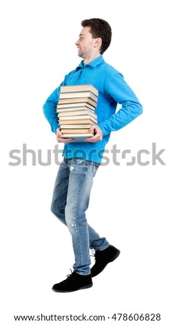 side view of going man carries a stack of books. walking young guy . curly-haired student in a blue sweater warm happily carries a stack of books.