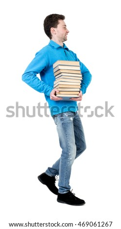side view of going  man carries a stack of books. walking young guy . Rear view people collection.  backside view of person.  Isolated over white background. The curly-haired student in a blue sweater