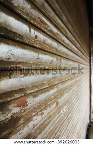 Side view of grunge metallic roller closed shutter of shop