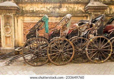 Side view of hand pulled cart rickshaws parked together. - stock photo