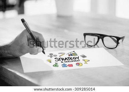 Side view of hand writing on white page on working desk against strategy and development doodle - stock photo