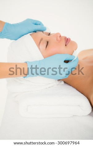 Side view of hands cleaning woman face with cotton swabs at spa center