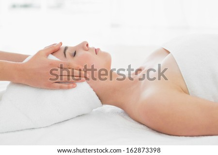 Side view of hands massaging a beautiful woman's face at beauty spa - stock photo