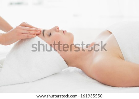 Side view of hands massaging a beautiful woman's forehead at beauty spa