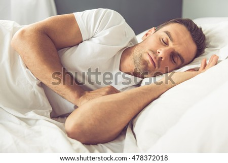 Side view of handsome man sleeping in his bed at home
