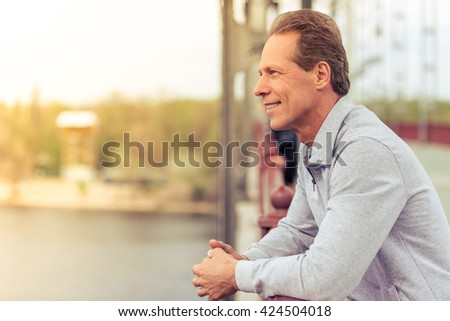 Side view of handsome middle aged man in sports uniform leaning on bridge and smiling while having break during morning run - stock photo