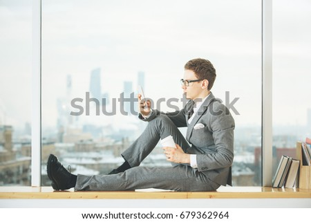Side view of handsome white man sitting on windowsill with city view and using smartphone. Social media concept