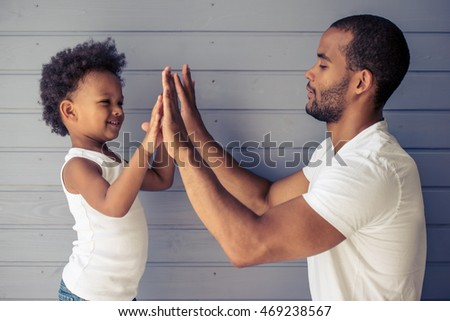 Side view of handsome young Afro American father and his cute child touching hands and smiling, standing before gray wall