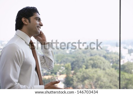 Side view of handsome young businessman using cellphone - stock photo