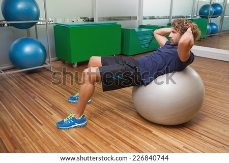 Side view of handsome young man doing abdominal crunches on fitness ball in gym - stock photo