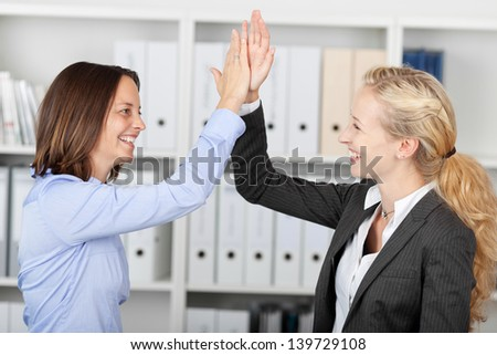 Side view of happy businesswomen fiving high five in office - stock photo