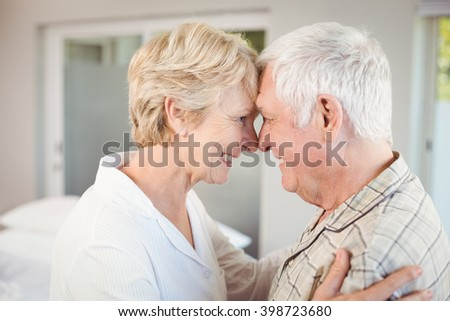 Side view of happy couple touching nose at home