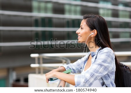 side view of happy female college student looking up - stock photo