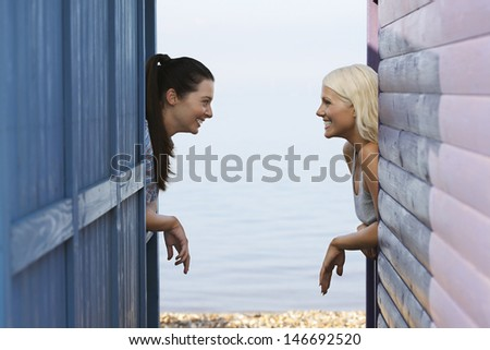 Side view of happy female friends looking at each other while leaning on balustrade of beach house - stock photo