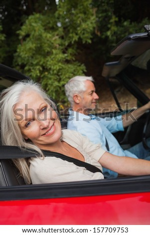 Side view of happy mature couple driving red cabriolet on sunny day