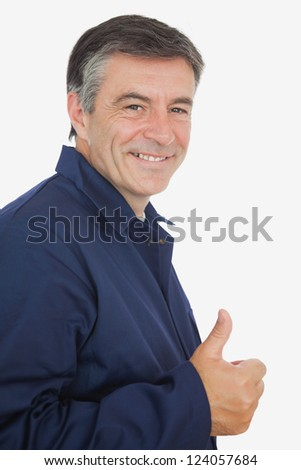 Side view of happy mature mechanic showing thumbs up sign over white background - stock photo