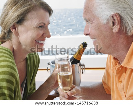 Side view of happy middle aged couple drinking champagne on yacht - stock photo