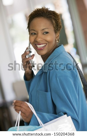 Side view of happy woman answering mobilephone in furniture store - stock photo