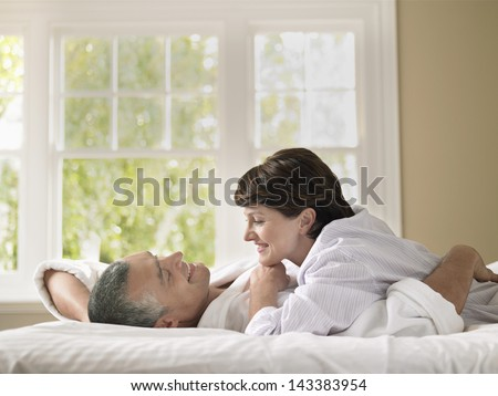 Side view of happy woman looking at husband while lying in bed - stock photo