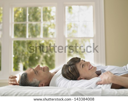 Side view of happy woman lying with husband while looking up in bed