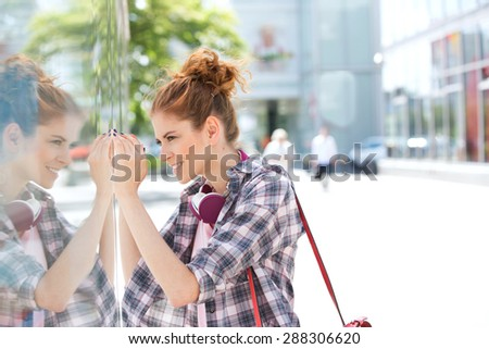 Side view of happy woman window shopping in city - stock photo