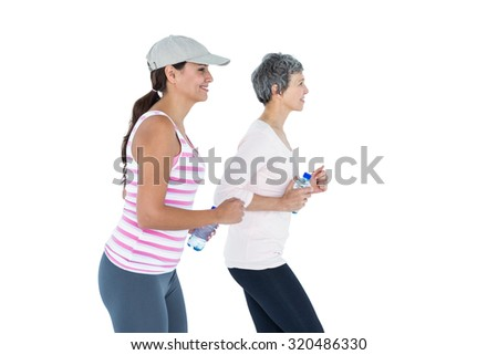 Side view of happy women with bottle jogging against white background - stock photo