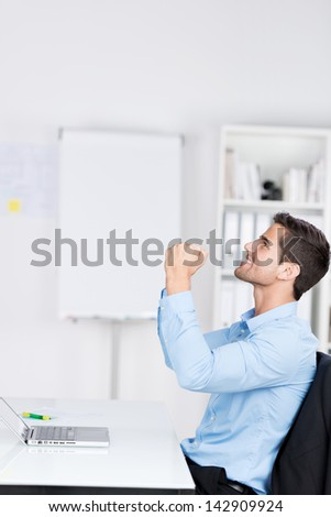 Side view of happy young businessman with clenched fists celebrating victory at desk in office - stock photo