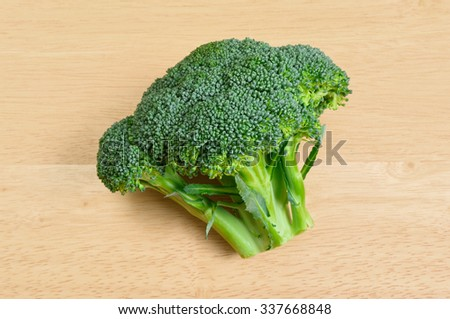 Side View of Head of Green Broccoli on Table - stock photo