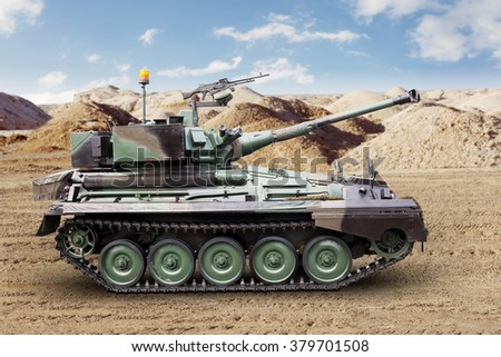 Side view of heavy military tank with a cannon walking on the desert  - stock photo