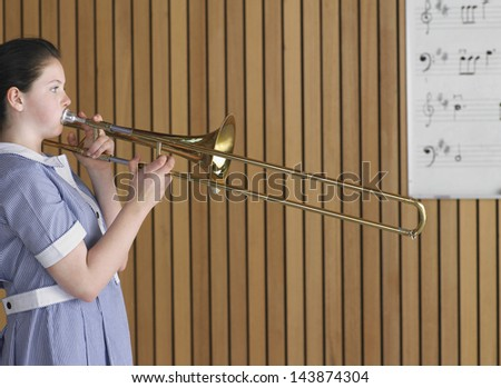 Side view of high school girl playing trombone in music class - stock photo