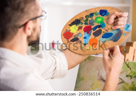 Side view of highly gifted painter while he is painting his picture. Close-up. - stock photo