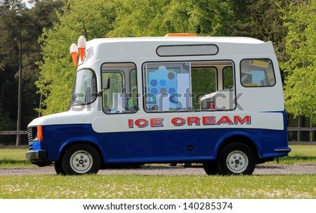 Side view of ice cream van in green countryside - stock photo