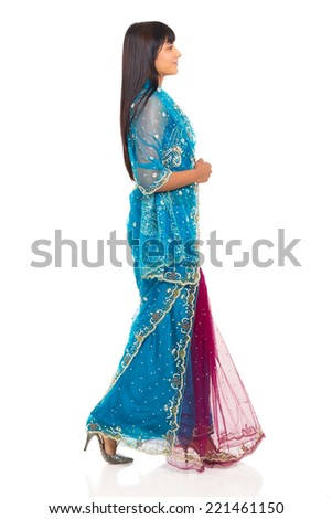 side view of indian woman in saree walking on white background - stock photo