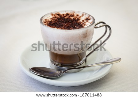 Side view of Italian coffee latte or cappuccino drink with a white saucer and spoon on a plain table. / Italian Coffee Latte - stock photo