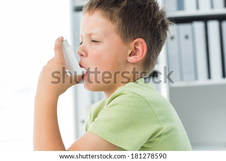 Side view of little boy using an asthma inhaler in clinic - stock photo