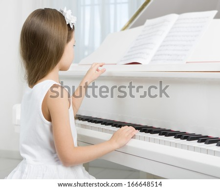 Side view of little girl in white dress playing piano. Concept of music study and art - stock photo