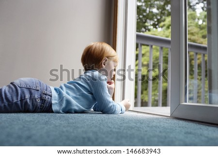 Side view of little girl looking out through balcony while lying on carpet at home